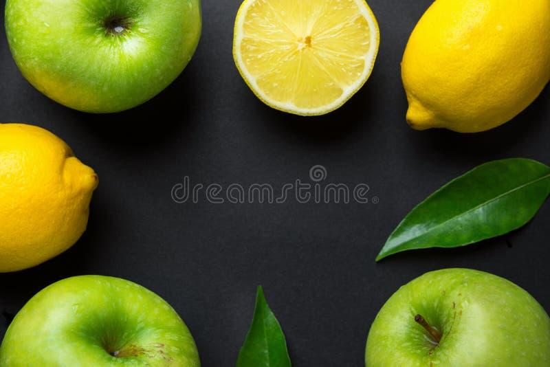 Feldzusammensetzung von den saftigen Zitronen der frischen rohen gr?nen organischen ?pfel verl?sst auf schwarzem Hintergrund Gesu lizenzfreies stockbild