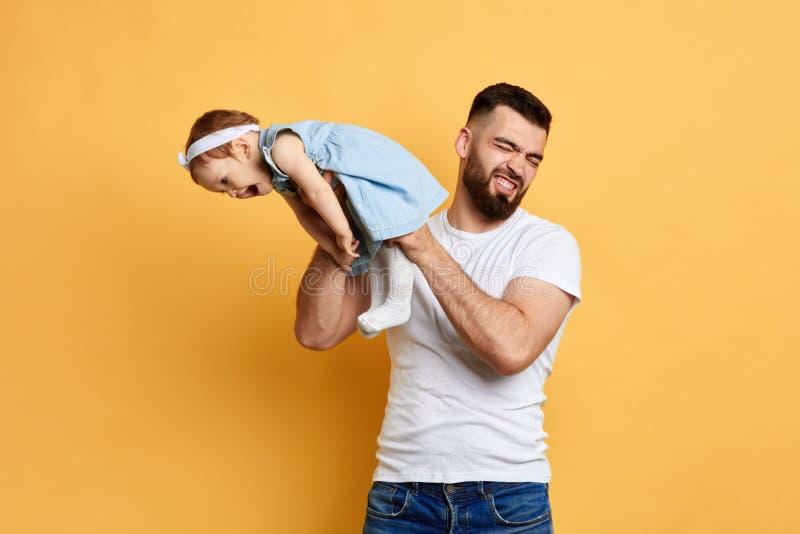 Felice bambino che soffia scoreggia mentre è trattenuto dal suo papà fotografia stock libera da diritti