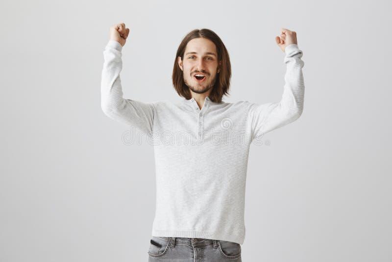 Felice di vedere punteggio del suo gruppo Colpo dell'interno del fan leale con capelli lunghi e della barba che alza i pugni chiu immagine stock