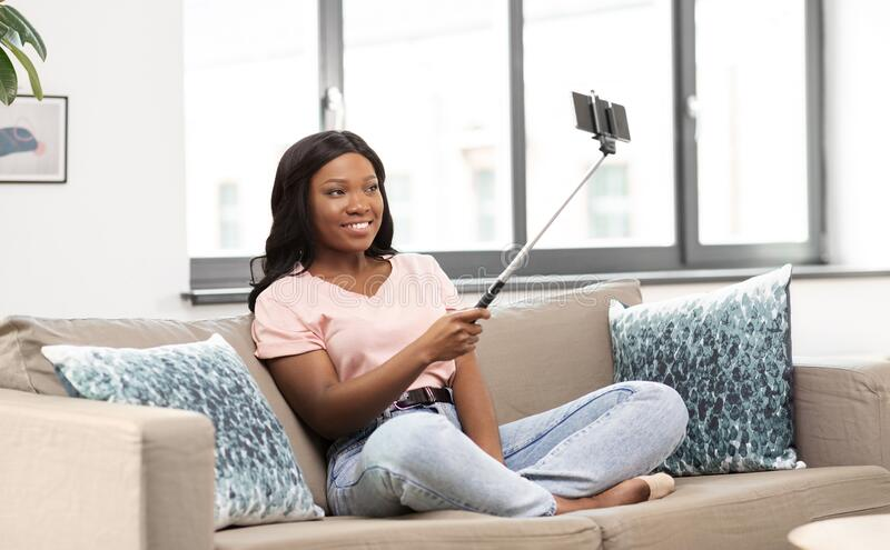 Felice donna africana americana che si fa selfie a casa fotografia stock