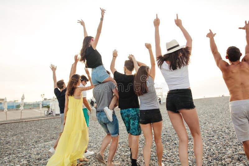Felice equipaggia e la passeggiata della donna al gruppo di spiaggia di amici che godono delle feste della spiaggia fotografia stock