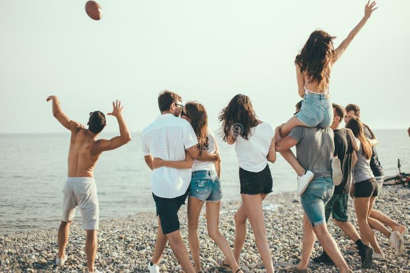 Felice equipaggia e la passeggiata della donna al gruppo di spiaggia di amici che godono delle feste della spiaggia immagine stock libera da diritti