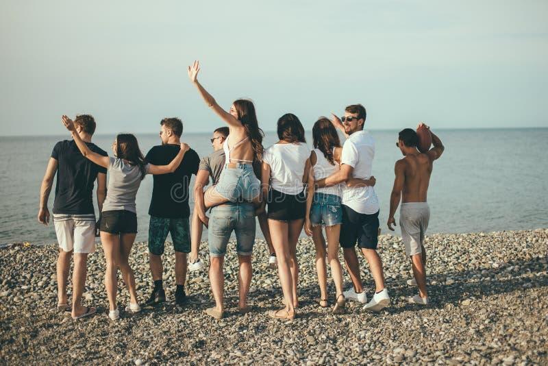 Felice equipaggia e la passeggiata della donna al gruppo di spiaggia di amici che godono delle feste della spiaggia immagini stock