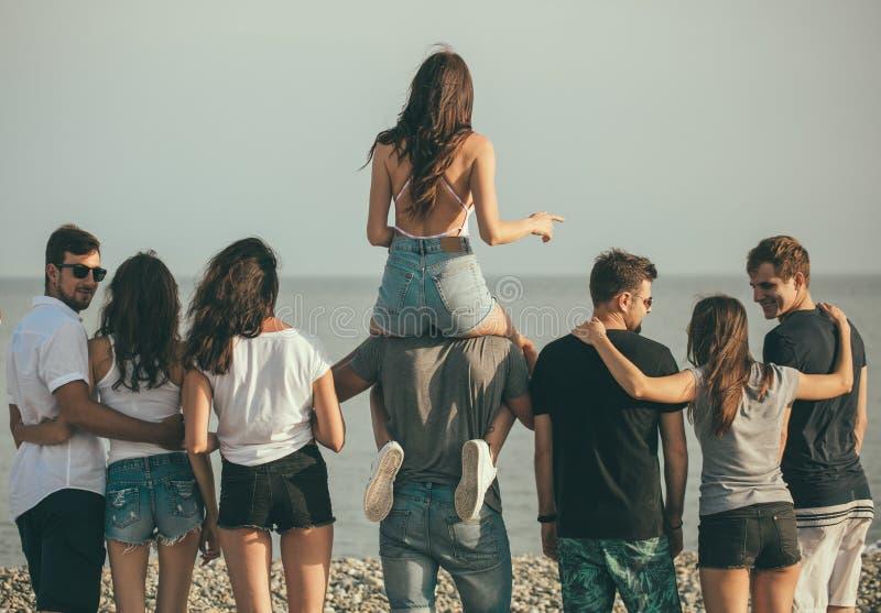 Felice equipaggia e la passeggiata della donna al gruppo di spiaggia di amici che godono delle feste della spiaggia fotografia stock libera da diritti