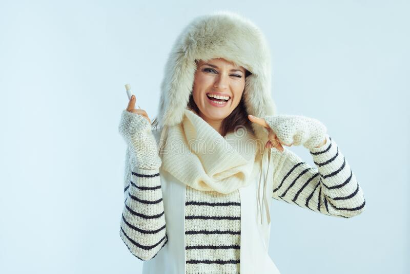 Felice femmina alla moda puntando sul rossetto igienico fotografia stock