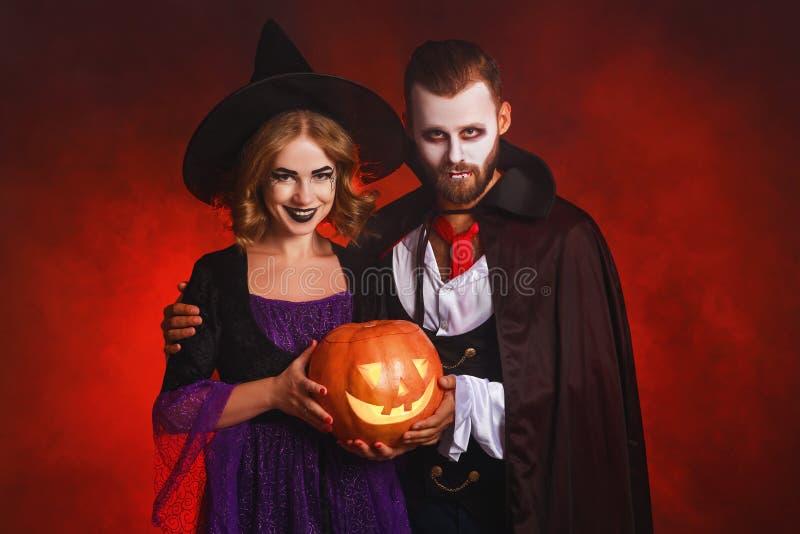 Felice Halloween! coppia di uomini e donne in un vampiro di Dracula e costumi da strega con una zucca sullo sfondo rosso scintill immagine stock libera da diritti