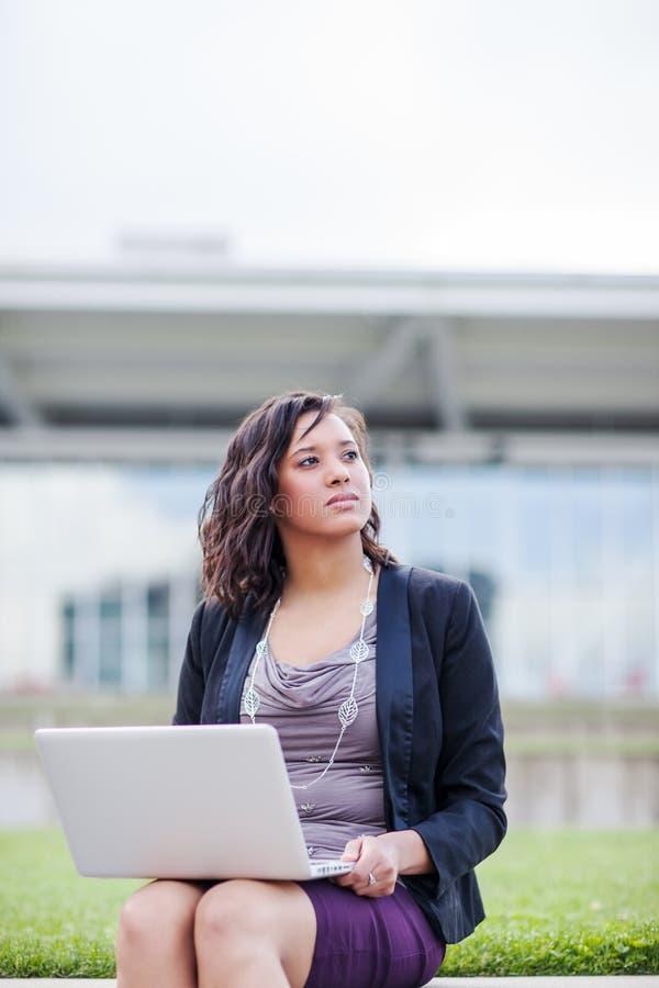 Felice imprenditrice afroamericana che lavora sul suo computer portatile fotografia stock