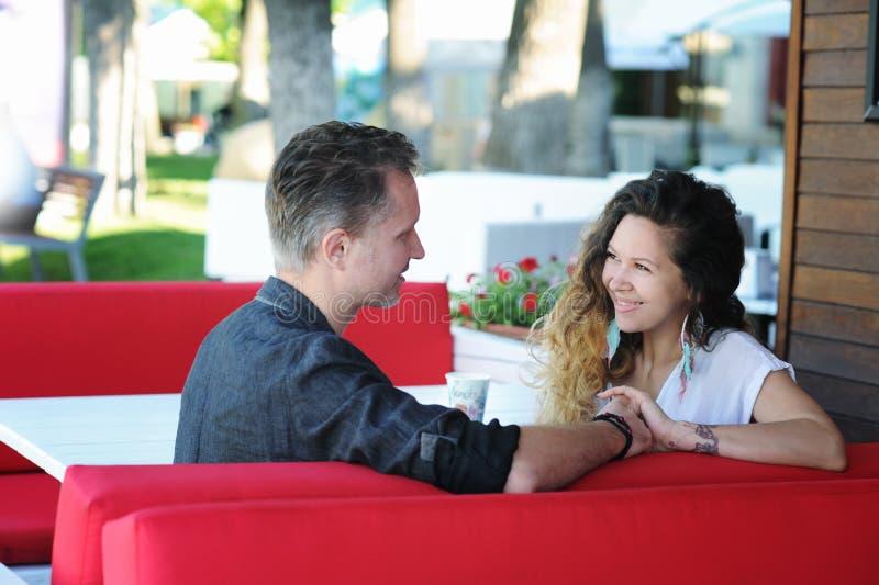 Felice nelle coppie di amore che si siedono in un caffè della via immagine stock libera da diritti