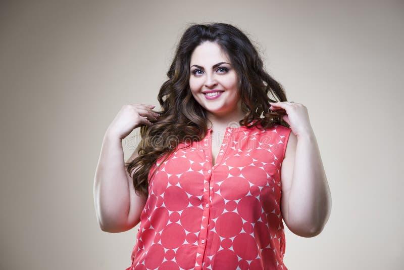 Felice più il modello di moda in abbigliamento casual, donna grassa su fondo beige, ente femminile di peso eccessivo di dimension fotografia stock