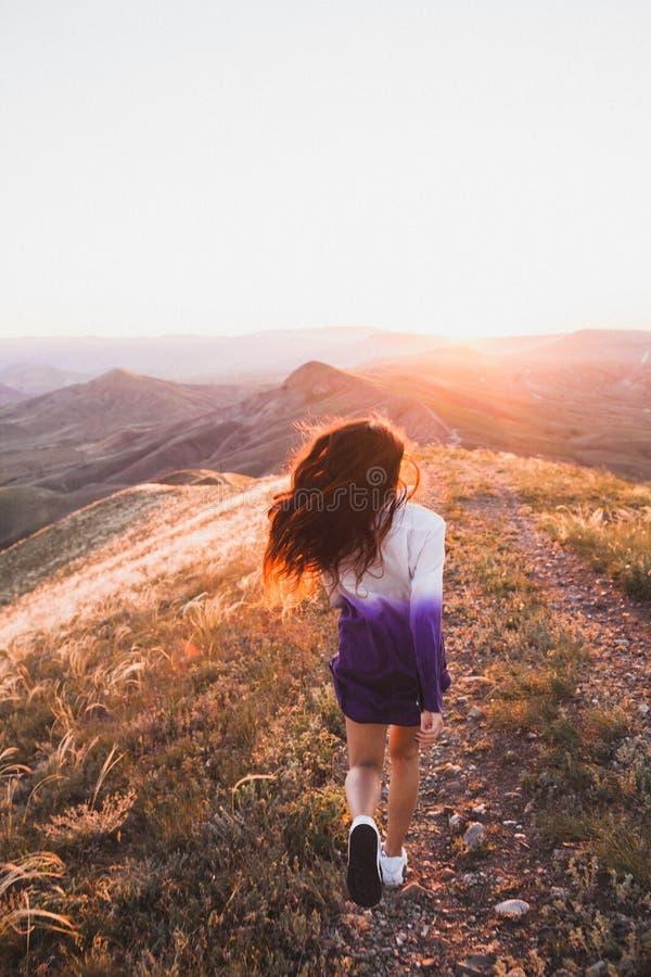 Felice ragazza che corre sotto la luce del tramonto Concetto di libertà fotografia stock libera da diritti