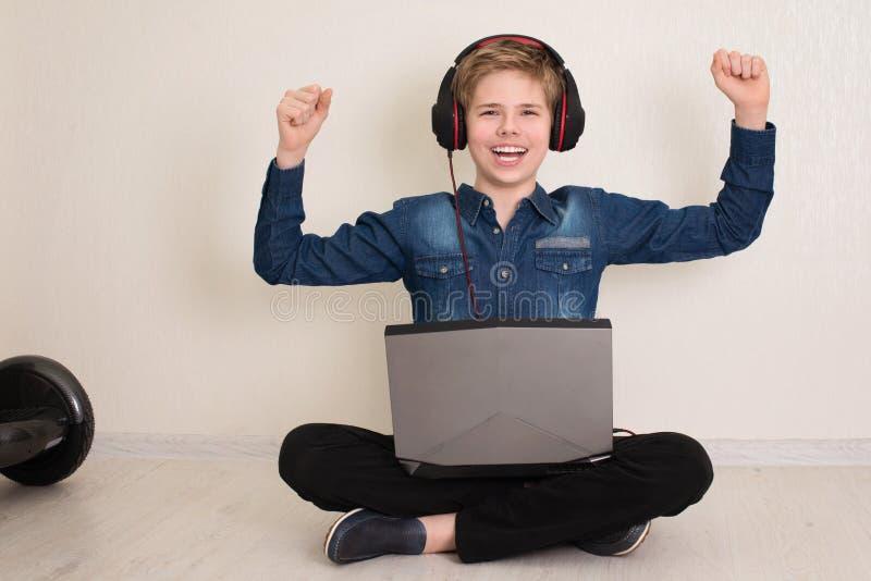 Felice ragazzo adolescente che lavora o gioca sul computer portatile mentre sta seduto sul pavimento con le gambe incrociate con  fotografie stock libere da diritti
