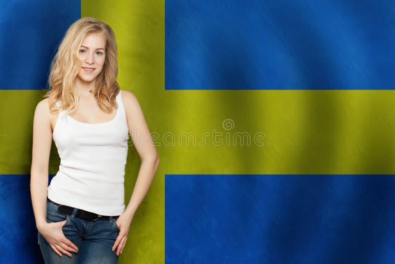 Felice studentessa bionda con bandiera svedese Viaggiare e imparare la lingua svedese immagine stock