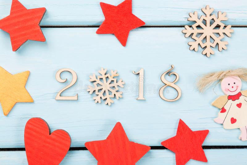 2018 Felices Año Nuevo Decoraciones de la Navidad rojas, estrellas amarillas, ángel, copo de nieve y corazón en fondo de madera a fotografía de archivo