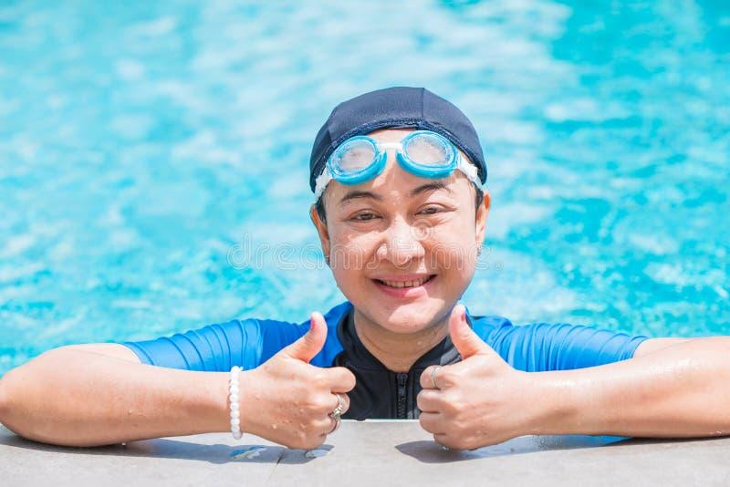 Felices de la mirada mayor de la mujer del deporte buenos gozan a nadar imagen de archivo