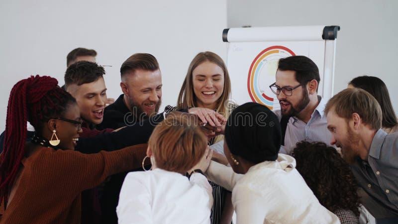 Felices empresarios multiétnicos unen sus manos para celebrar el éxito de los negocios con el joven jefe masculino Lugar de traba imagenes de archivo