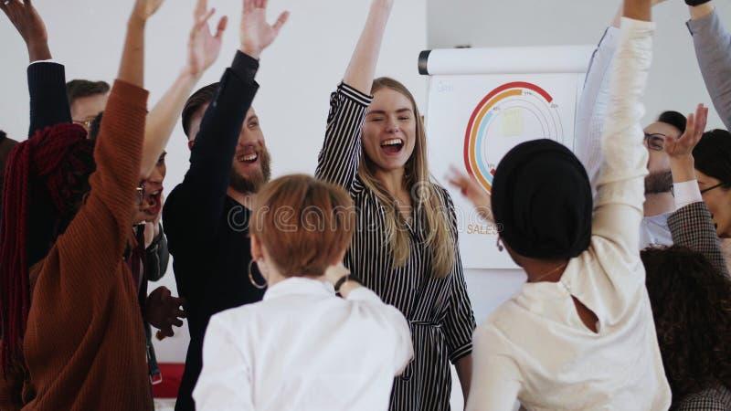 Felices empresarios multiétnicos unen sus manos para celebrar el éxito de los negocios con el joven jefe masculino Lugar de traba fotografía de archivo libre de regalías