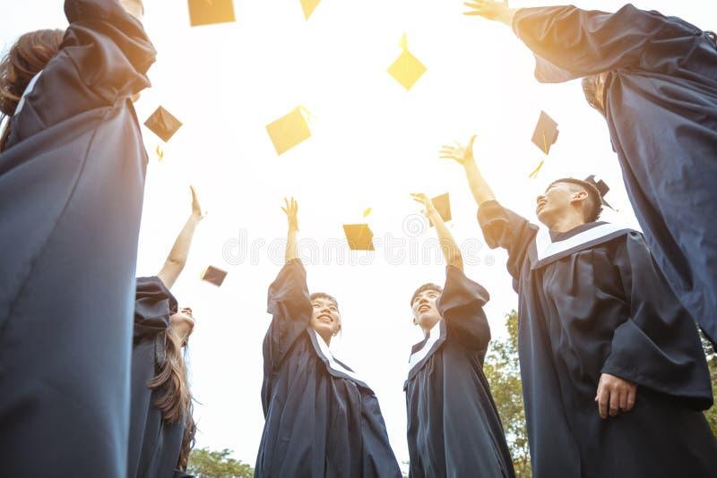 Felices estudiantes en batas de graduación celebrando en el campus universitario foto de archivo libre de regalías