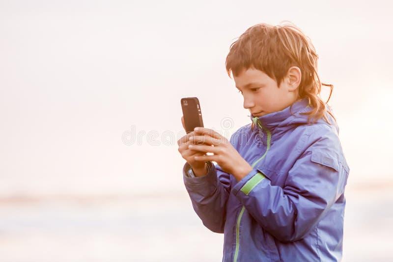 Felices jovenes preeteen al muchacho que mira el smth en la pantalla del teléfono, outdoo imagen de archivo
