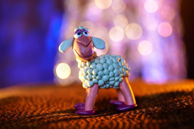 Felices ovejas del plasticine de la serie de la Navidad y de las luces borrosas fotos de archivo libres de regalías