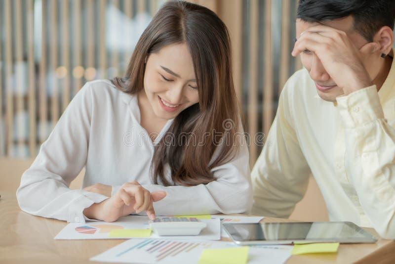 Felices parejas asiáticas sonríen después de calcular ingresos y gastos porque reciben ganancias de sus inversiones Conceptos de  imagen de archivo