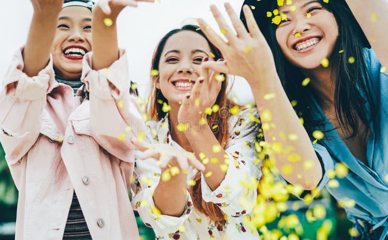 Felici amici asiatici che si divertono a gettare coriandoli all'aperto - giovani alla moda che festeggiano all'esterno fotografie stock libere da diritti