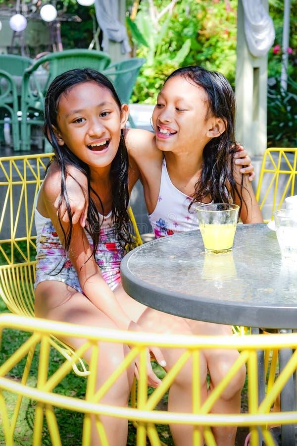 Felici sorrisi asiatici in costume da bagno che sorridono, ridono e si abbracciano a vicenda per passare del tempo insieme all'es fotografia stock