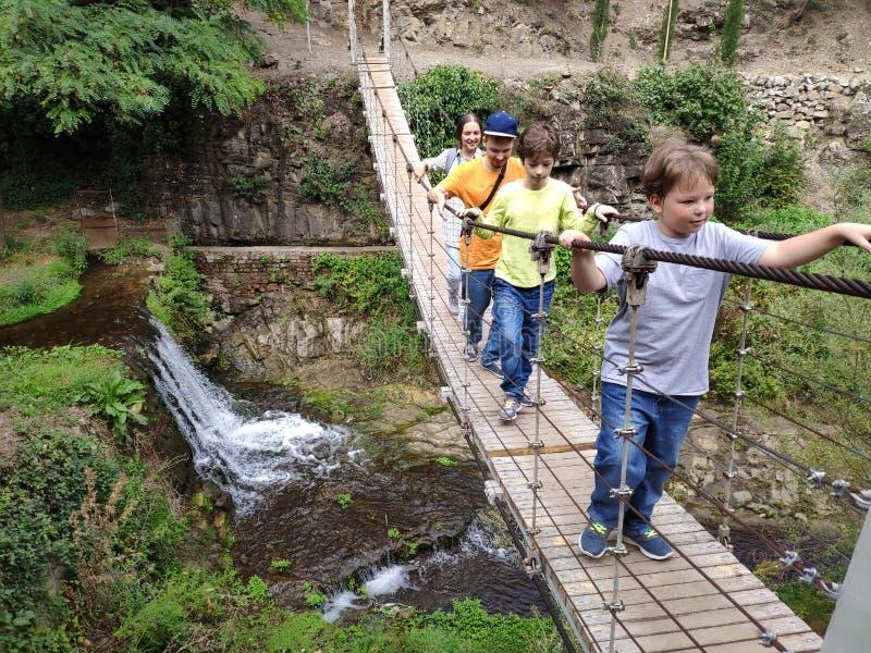 Felici viaggiatori, la famiglia sul ponte sospeso fotografia stock libera da diritti