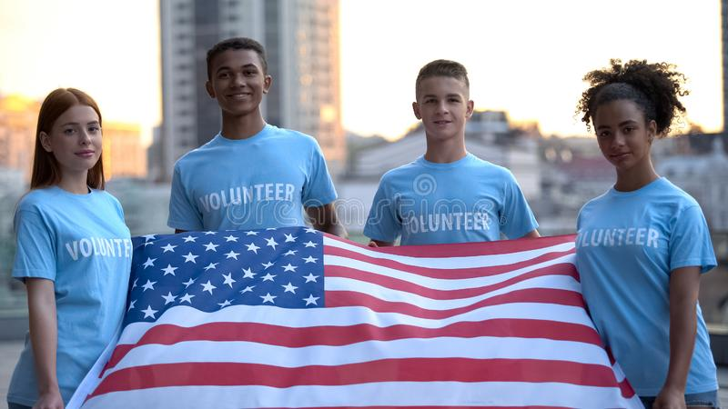 Felici volontari multi-razziali con bandiere americane, fondazione di beneficenza, aiuto fotografie stock libere da diritti