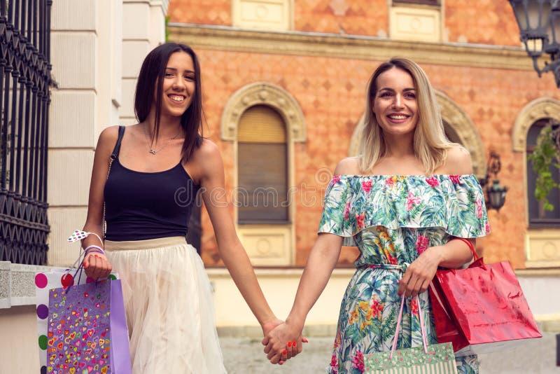 Felicidad, amigos, venta y mujeres concepto-sonrientes de la diversión con los bolsos de compras fotografía de archivo libre de regalías
