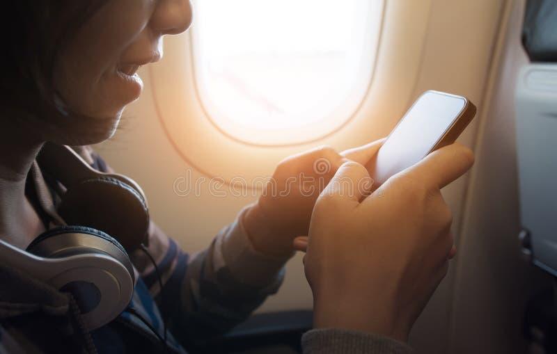 Felicidad de la muchacha asiática con el auricular usando smartphone imagenes de archivo