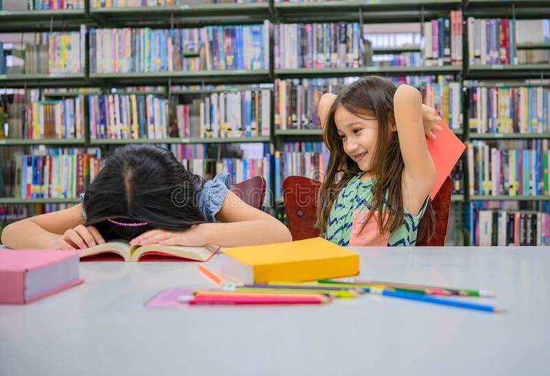 Felicidad dos chicas de la diversidad linda leyendo el libro y burlándose de golpear a un amigo durmiente en la biblioteca escola imagen de archivo libre de regalías