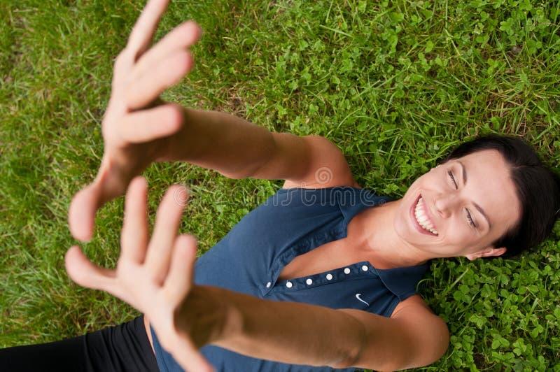 Felicidad - mujer que miente en hierba fotografía de archivo
