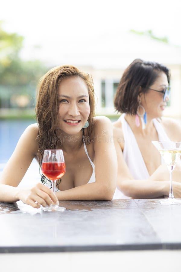 Felicidad sonriente dentuda hermosa de la cara del traje de baño de una mujer que lleva más joven en la piscina foto de archivo libre de regalías