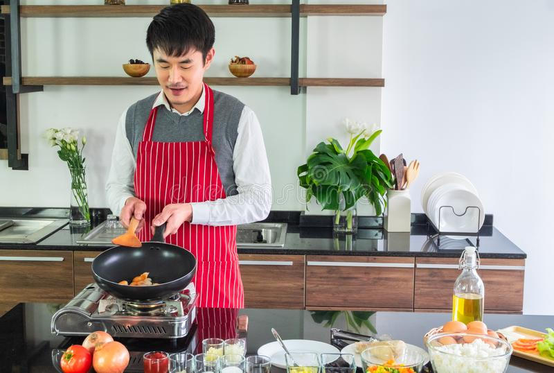 Felicidad sonriente hermosa, asiática del hombre joven Freír las salchichas en una cacerola para la comida foto de archivo