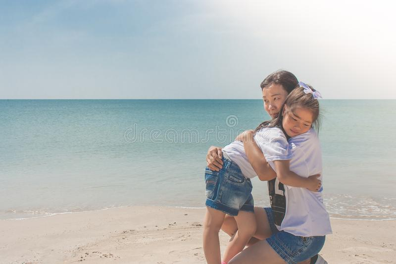 Felicidade de aperto e de sentimento da mulher e da criança na praia da areia com opinião do seascape no fundo fotografia de stock