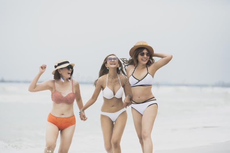 Felicidade de sorriso toothy vestindo da cara do roupa de banho da mulher asiática bonita alegre no beira-mar imagens de stock