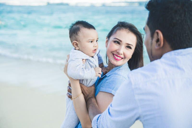 Felicidade pequena da família quando férias na praia foto de stock