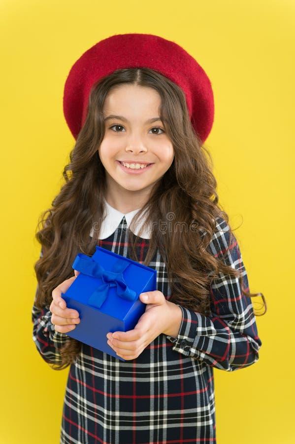 Felicidade real crian?a parisiense no fundo amarelo Compras crian?a com caixa atual menina feliz com cabelo encaracolado longo imagens de stock