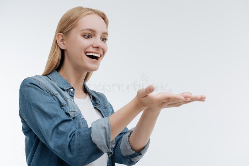 Felicità stupefacente di sensibilità della ragazza mentre presentando qualcosa immagine stock libera da diritti