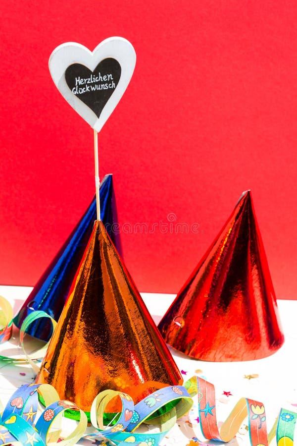 Felicitações, como o texto no coração, com chapéu do partido, backgroun vermelho foto de stock