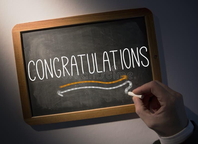 Felicitações da escrita da mão no quadro fotografia de stock