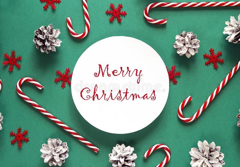 Felicitações do Natal com bastões de doces e cones do pinho no gree fotografia de stock
