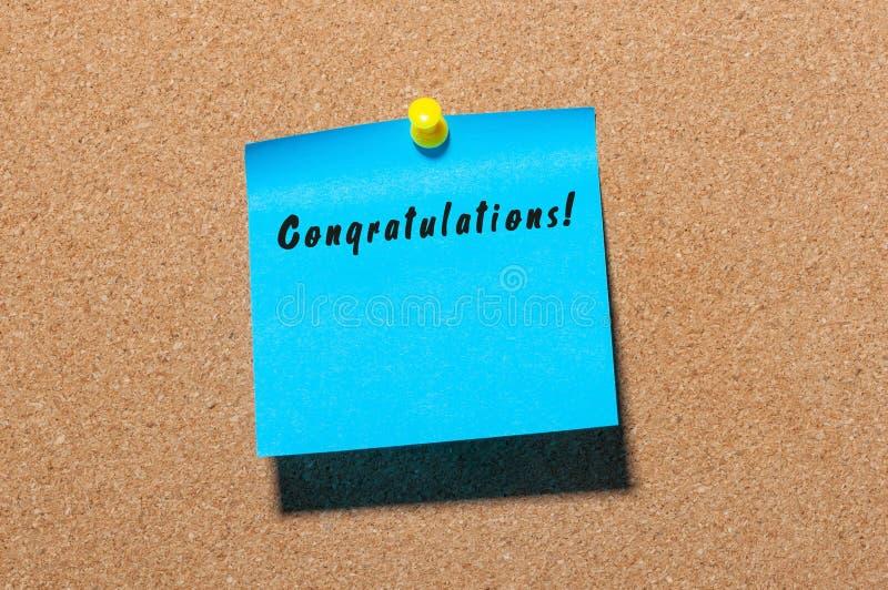 Felicitações - inscrição na etiqueta azul fixada ao quadro de mensagens da cortiça Com espaço vazio para o texto fotos de stock royalty free