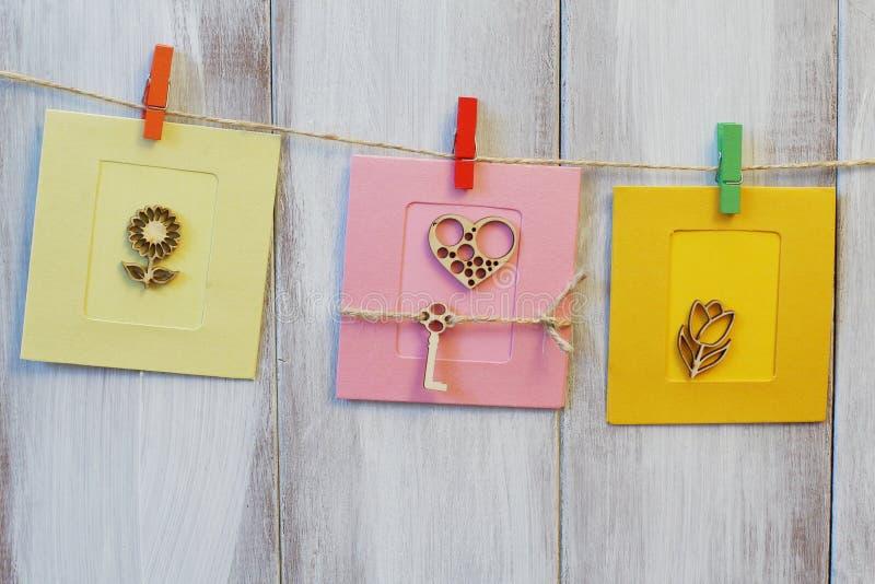 Felicitatie modieuze eigengemaakte kaarten op jutekoord Gestileerde houten gesneden bloemen op lichte en donkere gele gestileerde royalty-vrije stock afbeeldingen