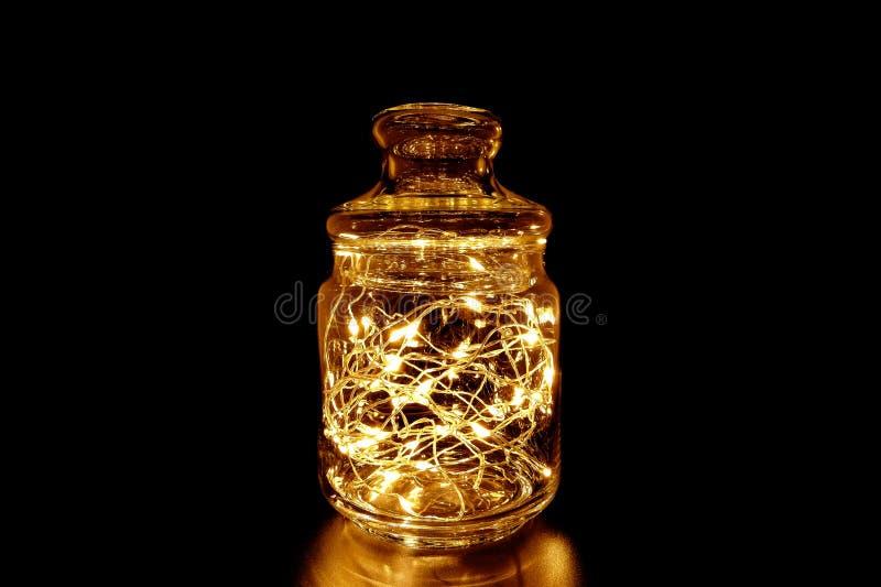 Felikt ljus i en exponeringsglaskrus på svart bakgrund royaltyfri foto