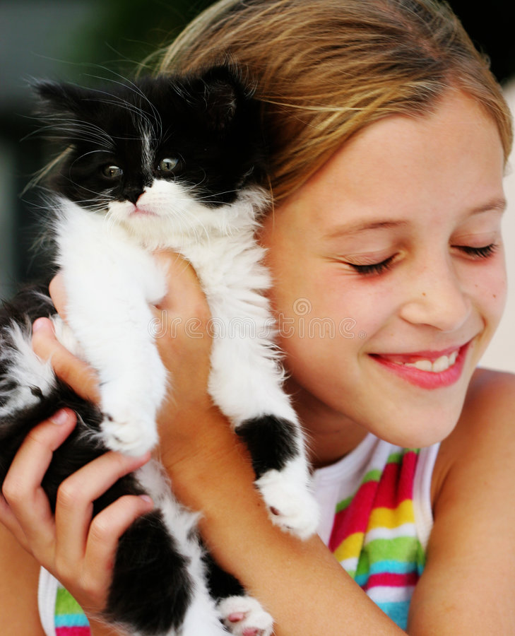 Feline Fine. Adorable kitten being cuddled by little girl