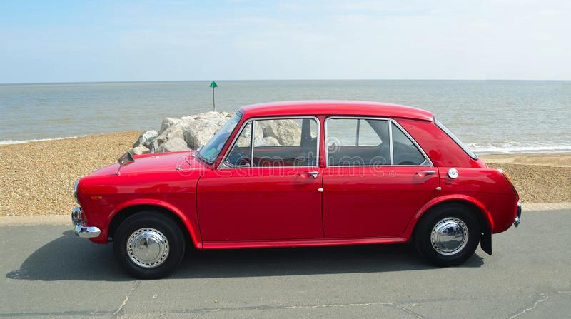 Classic Red Austin 1100 Motor Car parked on seafront promenade. royalty free stock image