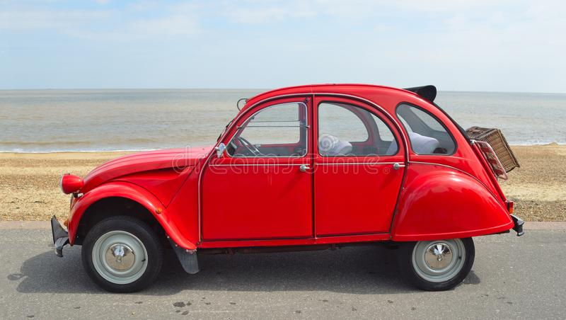 Classic Red Citroen 2CV deux chevaux parked on seafront promenade. stock photos
