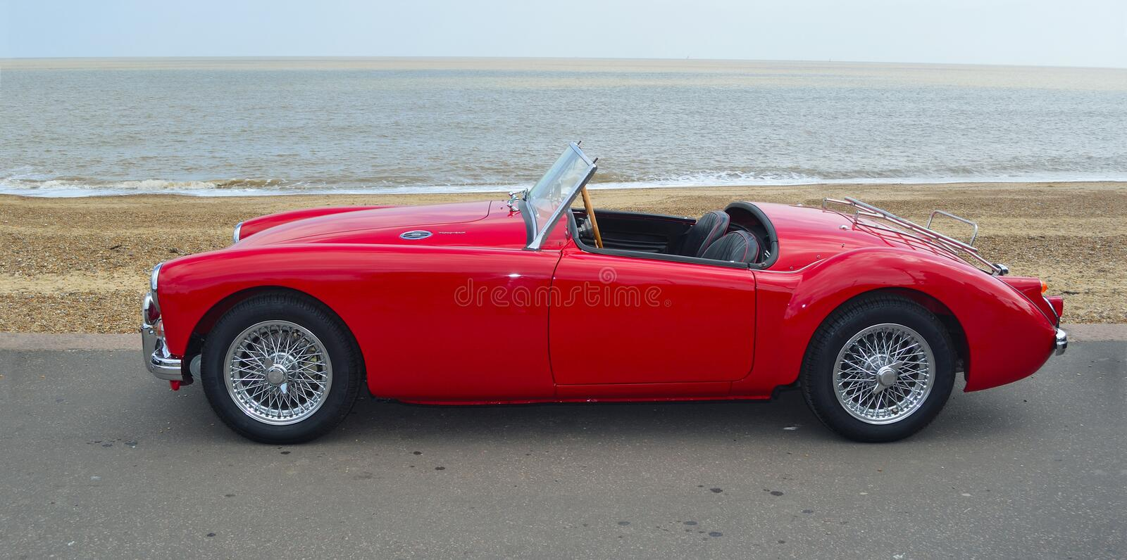 Classic Red MGA Car parked on seafront promenade with sea in background. stock image