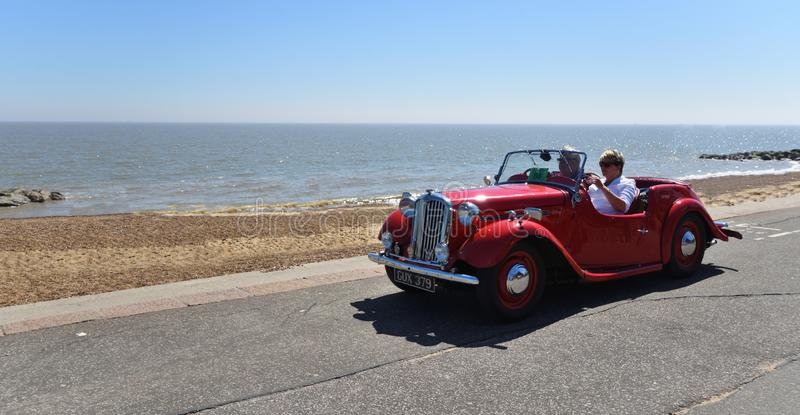 Classic Red Singer Convertible Motor Car being driven along Seafront Promenade. royalty free stock images